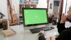 El hombre barbudo con mirada artística mira un vídeo en una pantalla verde almacen de metraje de vídeo