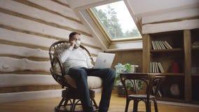 El hombre barbudo con el ordenador portátil bebe el café en el ático metrajes