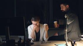 El hombre barbudo del colega masculino que cuida está trayendo se lleva el café a la mujer joven cansada que trabaja en el ordena almacen de metraje de vídeo
