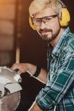 El hombre barbudo del inconformista joven brillante con las protecciones auditivas por las sierras del constructor del carpintero Fotos de archivo libres de regalías
