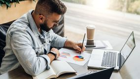 El hombre barbudo del inconformista se sienta en la tabla, trabajando en el ordenador portátil, y hace notas en la carta, gráfico foto de archivo