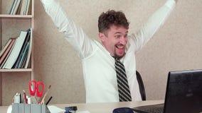 El hombre barbudo divertido del administrador de oficinas, trabaja vigoroso en el ordenador portátil metrajes