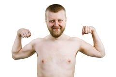 El hombre barbudo divertido muestra su bíceps Foto de archivo libre de regalías