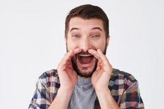 El hombre barbudo emocionado joven que lleva a cabo las manos acerca a la boca mientras que screami Imagenes de archivo