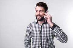 El hombre barbudo en camisa habla por el teléfono en el fondo blanco Fotos de archivo libres de regalías