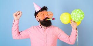El hombre barbudo en el casquillo del cumpleaños y los vidrios locos enormes que bailan, va de fiesta difícilmente, concepto del  Foto de archivo libre de regalías