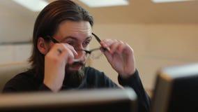 El hombre barbudo en oficina saca sus vidrios almacen de metraje de vídeo