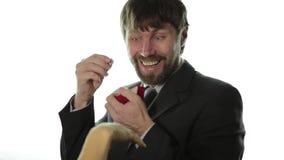 El hombre barbudo en un traje de negocios da un anillo en la caja roja y expresa diversas emociones almacen de metraje de vídeo