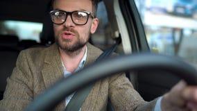 El hombre barbudo en vidrios conduce un coche y el griter?o en alguien cerca de ?l o afuera metrajes