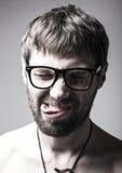 El hombre barbudo en vidrios juega al tonto hombre loco, expresión divertida Foto de archivo libre de regalías