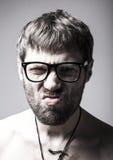 El hombre barbudo en vidrios juega al tonto hombre loco, expresión divertida Fotos de archivo
