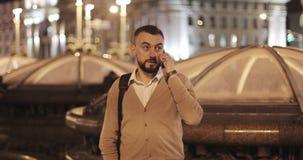 El hombre barbudo envejecido centro contesta a una llamada de teléfono en el fondo de una ciudad de la noche almacen de video