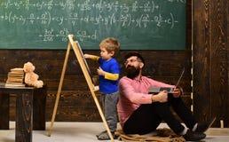 El hombre barbudo es profesor particular o profesor Niño del preescolar de las ayudas del profesor o del profesor particular Conf imagenes de archivo