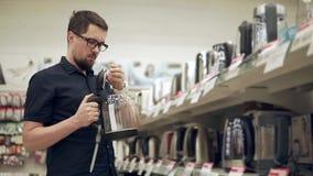El hombre barbudo está examinando la caldera eléctrica de cristal en un pasillo de la tienda del hardware almacen de video