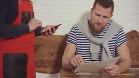 El hombre barbudo está pidiendo la comida en el café, mostrando al camarero en menú metrajes