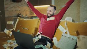 El hombre barbudo feliz está trabajando en casa con el ordenador portátil y está haciendo un trato acertado o gana el dinero gran almacen de metraje de vídeo