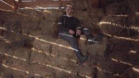 El hombre barbudo hermoso en vidrios con el pelo rubio que se sienta en el heno con una paja en boca entonces la escupe hacia fue almacen de metraje de vídeo
