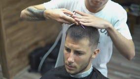 El hombre barbudo hermoso está mirando delantero mientras que haciendo que su pelo sea cortado por el peluquero la barbería metrajes