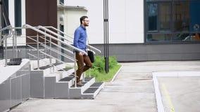 El hombre barbudo hermoso joven en camisa azul y pantalones marrones va afuera Estudiante que camina al aire libre feliz después almacen de video