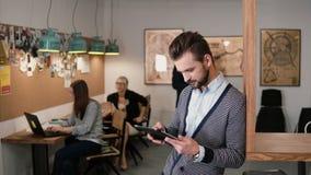 El hombre barbudo hermoso joven utiliza la tableta de la pantalla táctil en la oficina de lanzamiento moderna metrajes
