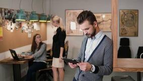 El hombre barbudo hermoso joven utiliza la tableta de la pantalla táctil en la oficina de lanzamiento moderna almacen de video