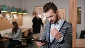 El hombre barbudo hermoso joven utiliza la tableta de la pantalla táctil en la oficina de lanzamiento moderna almacen de metraje de vídeo