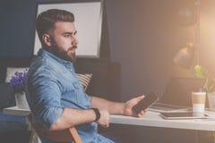 El hombre barbudo joven del freelancer en camisa del dril de algodón se está sentando en casa en la tabla, sosteniendo el teléfon imagenes de archivo