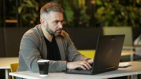 El hombre barbudo joven del inconformista, empresario Sits en el sof? en la mesa de centro, utiliza el ordenador port?til con la  metrajes