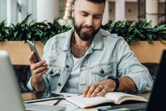 El hombre barbudo joven del inconformista se sienta en café delante de los ordenadores, lee notas en cuaderno mientras que sostie foto de archivo libre de regalías