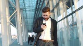 El hombre barbudo joven elegante camina abajo del terminal de aeropuerto, utiliza su teléfono, sorpresas con el mensaje, saca metrajes