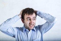 El hombre barbudo joven en el hombre azul de la camisa que lleva a cabo su cabeza y trastorno mira a un lado mirada del pánico imagenes de archivo