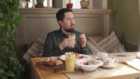 El hombre barbudo joven está bebiendo el jugo a través de la paja en un desayuno en café almacen de video