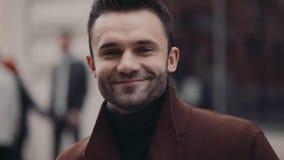 El hombre barbudo joven se coloca en la calle apretada y sonríe hacia la cámara Equipo elegante, moda masculina moderna almacen de video