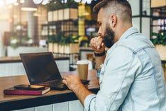 El hombre barbudo joven se está sentando en el café, mecanografiando en el ordenador portátil El Blogger trabaja en café El indiv imagen de archivo libre de regalías