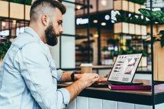 El hombre barbudo joven se está sentando en el café, mecanografiando en el ordenador portátil con las cartas, los gráficos, diagr imagen de archivo libre de regalías