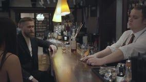 El hombre barbudo joven y la mujer morena irreconocible que se sientan en el contador de la barra Alcohol de mezcla del camarero  metrajes