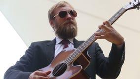 el hombre barbudo juega el acorde de la guitarra y sale metrajes