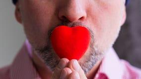 El hombre barbudo lleva a cabo el corazón rojo con los fingeres en sus labios, cierre para arriba fotografía de archivo