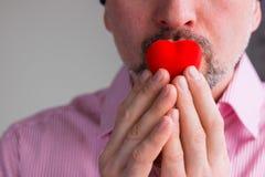 El hombre barbudo lleva a cabo el corazón rojo con los fingeres en sus labios, cierre para arriba fotos de archivo