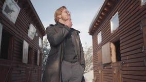El hombre barbudo pensativo en los vidrios que frotan ligeramente su barba que se coloca entre dos casas de madera se cierra para almacen de video