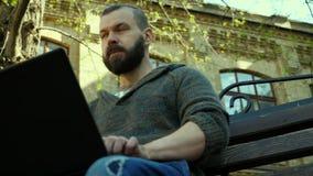 El hombre barbudo que mecanografía en un ordenador portátil afuera en un banco almacen de video