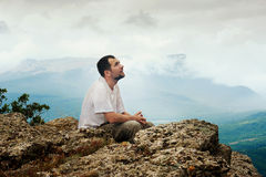 El hombre barbudo se sienta encima de la montaña Fotografía de archivo libre de regalías