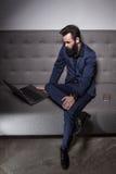 El hombre barbudo se vistió en traje y con Internet de la ojeada del ordenador portátil; Imagenes de archivo