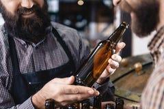 El hombre barbudo sostiene la botella vacía prevista para la cerveza del arte cerca de cervecería Botella de cerveza vacía imagen de archivo