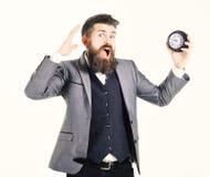 El hombre barbudo sostiene el reloj y grita Registre, demasiado ocupado, falta de tiempo, intemporal, prisa, ningún negocio del t imagenes de archivo