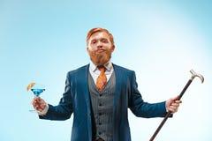 El hombre bardado en un traje que sostiene el bastón imagenes de archivo