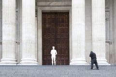 El hombre barre pasos de la catedral del ` s de San Pablo cerca de la estatua de los wi de Cristo Imágenes de archivo libres de regalías