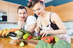 El hombre bastante perezoso está mirando a su esposa el preparar de la comida fotografía de archivo