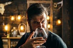 El hombre bebe el brandy o el whisky Traje que lleva del hombre barbudo y brandy o coñac de consumición del whisky El Sommelier p fotografía de archivo