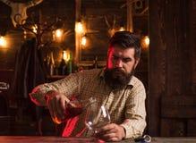 El hombre bebe el brandy o el whisky Traje que lleva del hombre barbudo y brandy o coñac de consumición del whisky El Sommelier p imagen de archivo libre de regalías